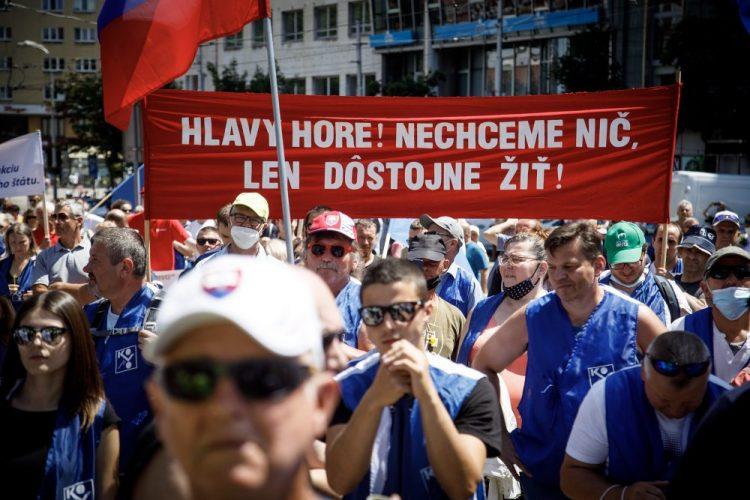 Účastníci s transparentom počas verejného protestného zhromaždenia Odborového zväzu (OZ) KOVO za zastavenie rozvratu sociálneho štátu na Námestí SNP v Bratislave. Bratislava, 26. jún 2021 (Foto: SITA/Branislav Bibel)